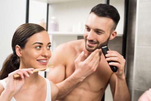 man shaving next to women in bathrom